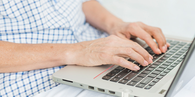 Older person typing on laptop