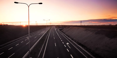 Motorway at sunset with large tall lights