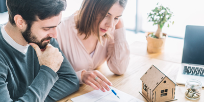 Couple filling out document looking puzzled with model house